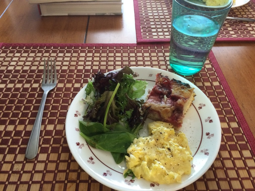 Cheesy scrambled eggs, salad greens, leftover long-cake
